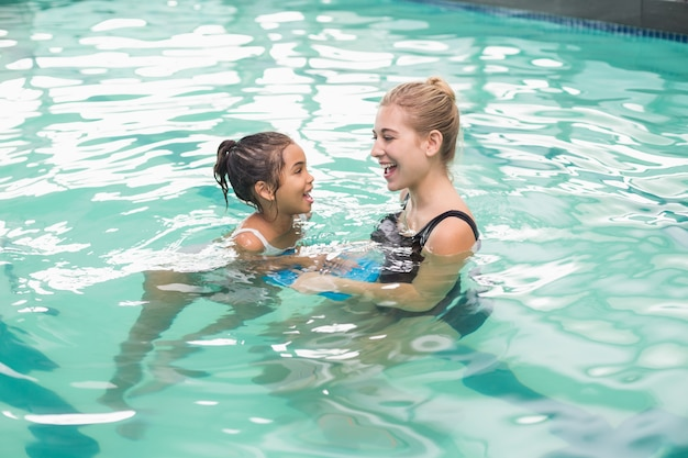 Jolie petite fille apprend à nager avec l'entraîneur