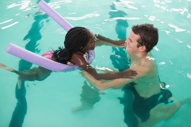 Jolie petite fille, apprendre à nager avec l'entraîneur