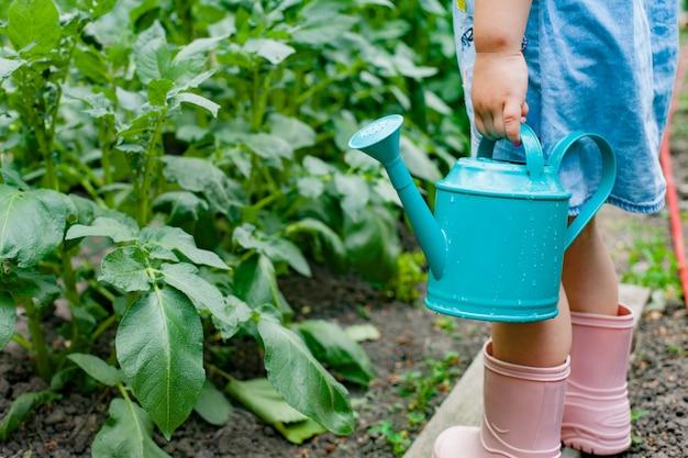 Jolie petite fille arrosant les plantes d'un arrosoir dans le jardin