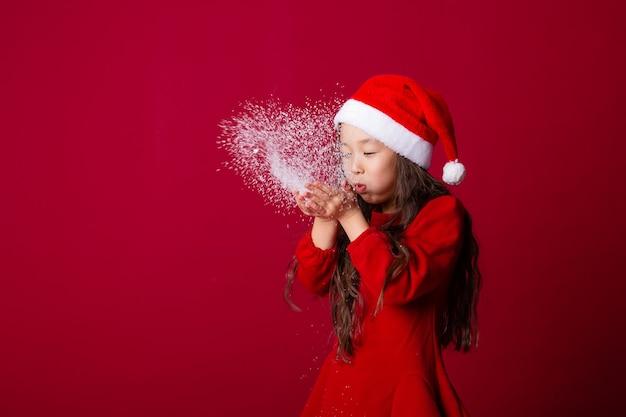 Jolie petite fille asiatique dans un bonnet de noel souffle la neige de ses paumes sur fond rouge