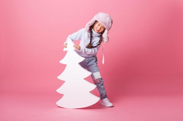 Une jolie petite fille asiatique dans un chapeau d'hiver se tient à côté d'un arbre de noël sur fond rose. concept d'hiver, espace pour le texte