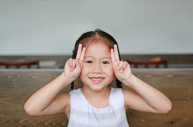 Jolie petite fille asiatique avec une expression semblable à un lapin allongé sur la table en bois avec regarder la caméra