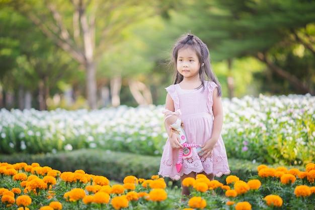 Jolie petite fille asiatique avec une poupée dans le jardin
