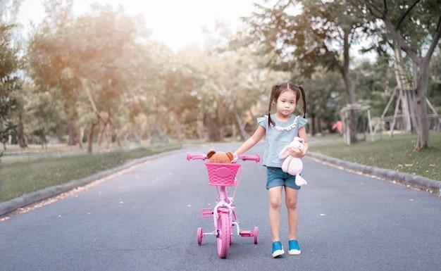 Jolie petite fille asiatique avec une poupée dans le parc