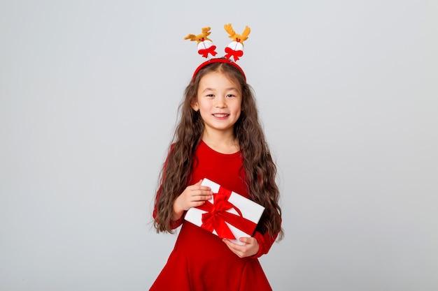 Jolie petite fille asiatique vêtue d'une robe rouge tient une boîte-cadeau sur l'espace de texte de concept de noël en arrière-plan