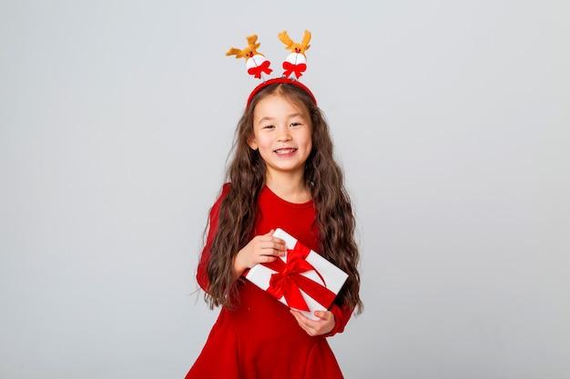 Jolie petite fille asiatique vêtue d'une robe rouge tient une boîte-cadeau espace de texte concept de noël