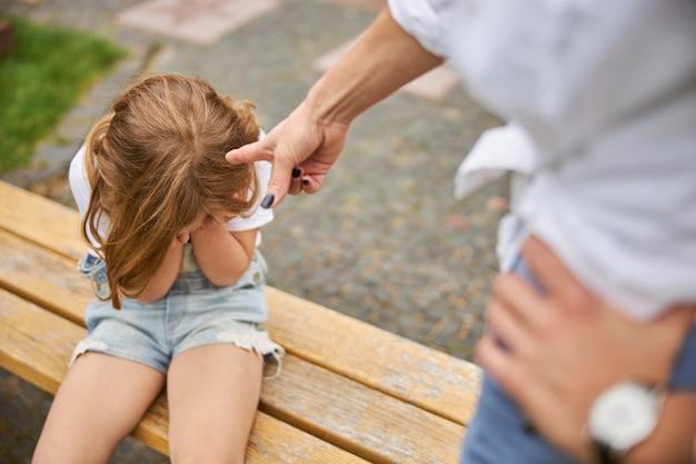 Jolie petite fille assise sur le banc en bois et pleurant près de la mère