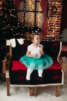 Jolie petite fille assise sur un canapé en bois recouvert de plaid