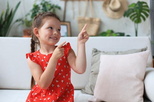 Jolie petite fille assise sur un canapé confortable et pointant du doigt quelque chose d'intéressant.
