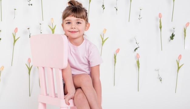 Jolie petite fille assise sur une chaise
