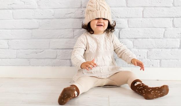 Jolie petite fille assise à côté d'un mur de briques