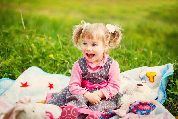Jolie petite fille assise sur l'herbe un jour d'été ensoleillé
