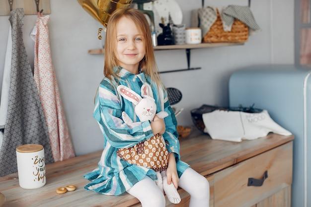 Jolie petite fille assise à la maison
