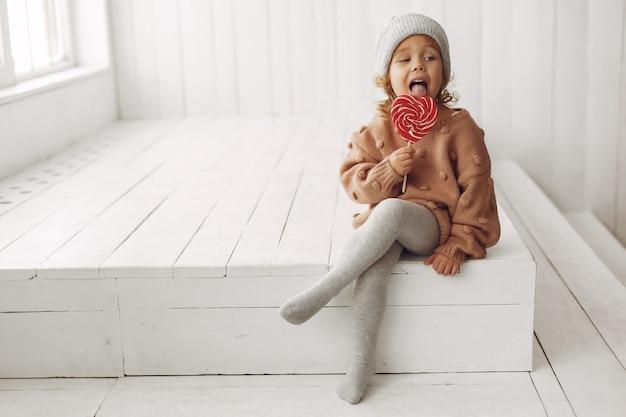Jolie petite fille assise et manger des bonbons