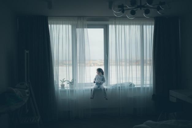 Jolie petite fille assise sur le rebord de la fenêtre