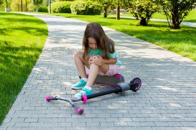 Jolie petite fille assise sur le sol après être tombée de son scooter au parc de l'été.