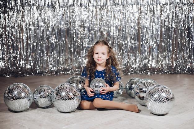 Jolie petite fille assise sur le sol tout en tenant une boule disco