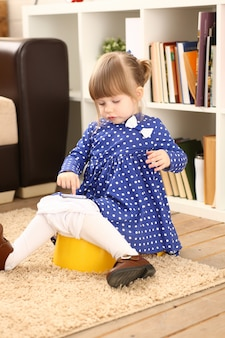 Jolie petite fille assise sur son pot de chambre