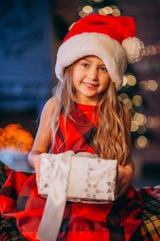 Jolie petite fille au bonnet de noel déballant le cadeau de noël