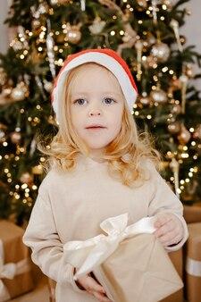 Jolie petite fille au chapeau de père noël sous l'arbre de noël avec boîte cadeau. bonnes vacances, nouvelle année. soirée d'hiver chaleureuse et chaleureuse à la maison. temps de noël