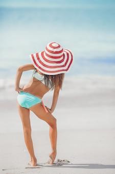 Jolie petite fille au chapeau sur la plage pendant les vacances des caraïbes