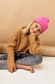 Jolie petite fille au chapeau rose assise sur le sol
