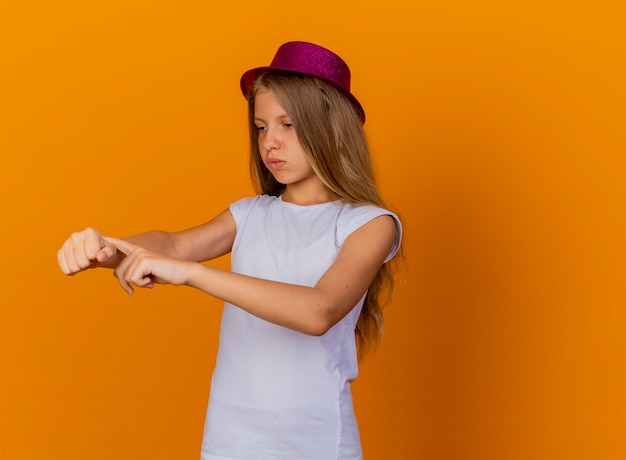 Jolie petite fille au chapeau de vacances pointant sur sa main rappelant que le temps était insatisfait, concept de fête d'anniversaire