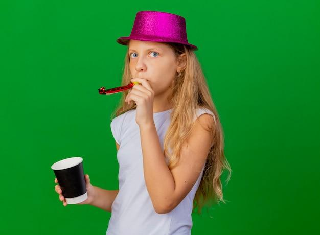 Jolie petite fille au chapeau de vacances tenant un sifflet soufflant smartphone
