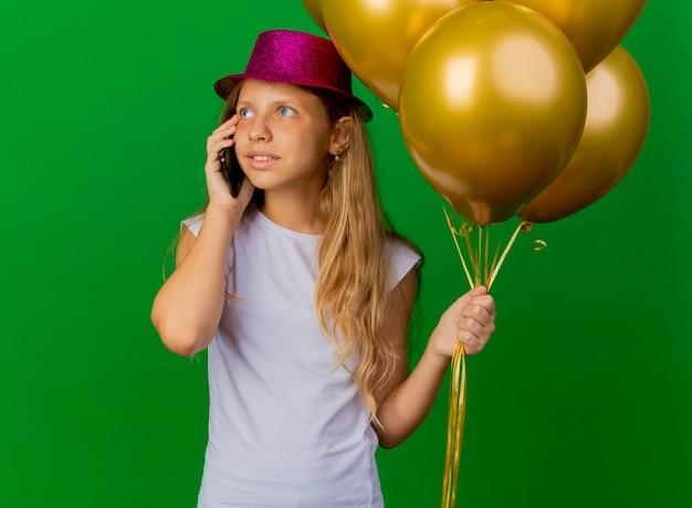 Jolie petite fille au chapeau de vacances tenant le smartphone