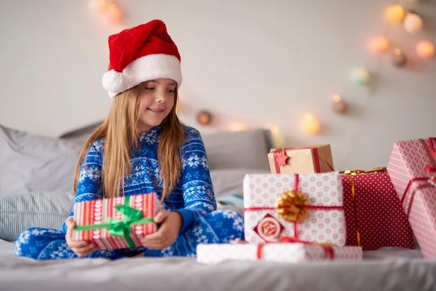 Jolie petite fille au lit avec des cadeaux de noël
