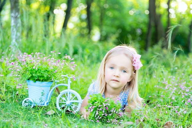 Jolie petite fille aux cheveux blonds allongé sur l'herbe dans le jardin un jour d'été