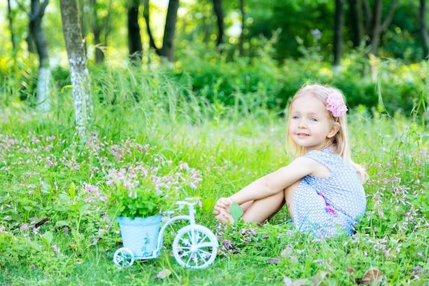 Jolie petite fille aux cheveux blonds assis sur l'herbe dans le jardin un jour d'été et rêvant