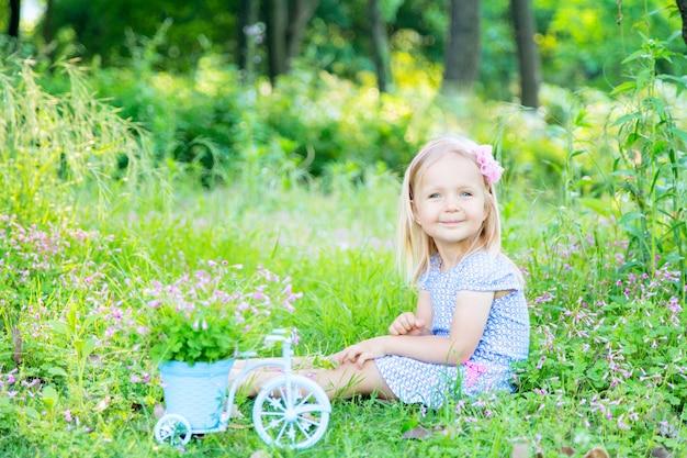 Jolie petite fille aux cheveux blonds assis sur l'herbe dans le jardin un jour d'été