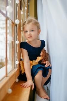 Jolie petite fille aux cheveux blonds en robe bleue tient son joli jouet et s'assoit dans la chambre de bébé sur un rebord de fenêtre et sourit