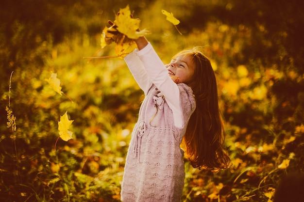 Jolie petite fille aux cheveux rouges joue avec des feuilles mortes