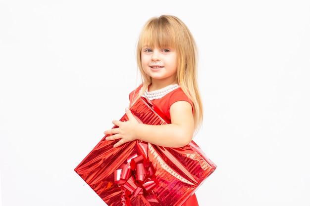 Jolie petite fille aux cheveux rouges tenant la boîte actuelle