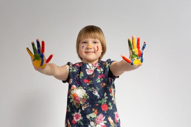 Jolie petite fille aux mains peintes colorées sur blanc isolé