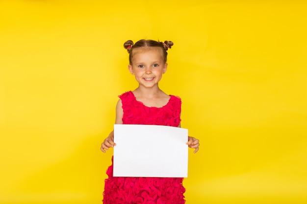 Jolie petite fille aux pieds nus avec deux petits pains et en robe d'été rose vif posant avec une liste de papier blanc sur fond jaune. espace copie