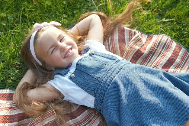 Jolie petite fille aux yeux fermés allongée sur l'herbe verte en été en faisant une sieste.