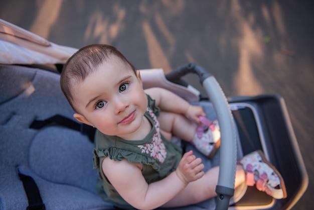 Une jolie petite fille aux yeux verts dans une robe est assise dans une poussette dans un parc verdoyant. portrait en gros plan d'un enfant regardant la caméra.