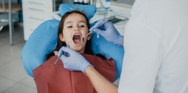Jolie petite fille ayant une chirurgie des dents par un stomatologue pédiatrique.