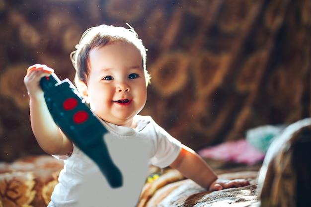 Jolie petite fille de bébé debout près du lit et jouant avec le jouet en plastique coloré mode rétro-éclairage. la poussière sur la tête