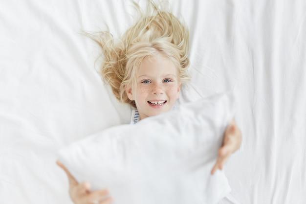 Jolie petite fille blonde au lit