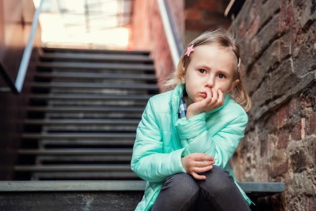 Jolie petite fille blonde caucasienne à la mode assise avec un regard pensif sur l'escalier en fer en regardant la caméra.
