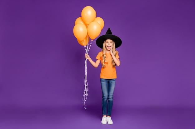 Jolie petite fille blonde avec un chapeau de sorcière et des ballons