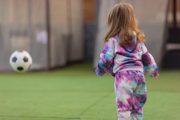 Jolie petite fille blonde en chemise rose jetant un ballon de foot en riant.