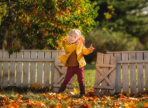 Jolie petite fille blonde danse dans le parc en automne