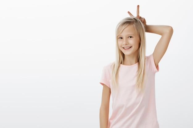 Jolie petite fille blonde souriante et faire des oreilles de lapin avec les doigts derrière la tête