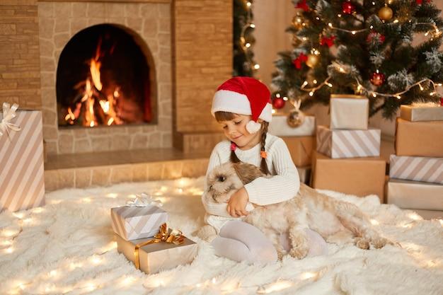Jolie petite fille en bonnet de noel étreignant avec chien sur fond de bel arbre de noël