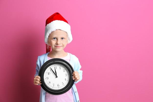 Jolie petite fille en bonnet de noel avec horloge sur fond de couleur. notion de compte à rebours de noël